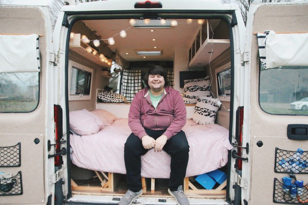 Shane sitting at the rear of the campervan